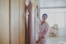 Die Schwester der Braut beim Abhängen der Kleider für eine Weinguthochzeit in Würzburg, fotografiert von Conny Schöffmann Photography, der Hochzeitsfotografin aus Würzburg