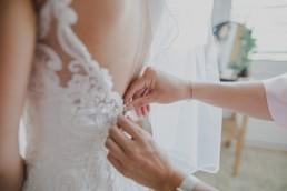 Die Schwester der Braut einer Weingut-Hochzeit schließt die letzten Knöpfe des Brautkleides fotografiert von Würzburger Hochzeitsfotografin Conny Schöffmann Photography