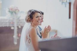 Fröhliches Brautpaar bei der kirchlichen Trauung an ihrem Hochzeitstag von Conny Schöffmann Photography