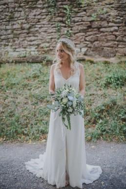 Braut steht mit natürlichem Brautstrauss vor einer Ruine im Freien fotografiert von Hochzeitsfotografin Conny Schöffmann Photography aus Würzburg