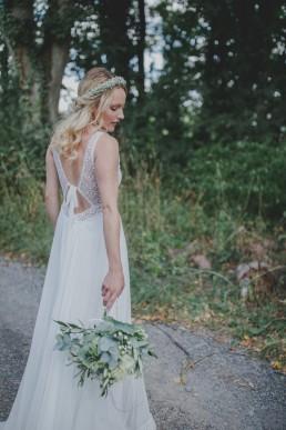 Natürliche Braut mit Brautstrauss in der Hand blickt unter Freiem Himmel stimmungsvoll nach unten fotografiert von Hochzeitsfotografin Conny Schöffmann Photography, Würzburg