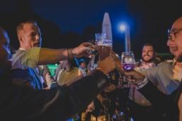 Entspannte Gäste stoßen im Freien mit ihren Getränken an fotografiert von Hochzeitsfotografin Conny Schöffmann Photography aus Würzburg