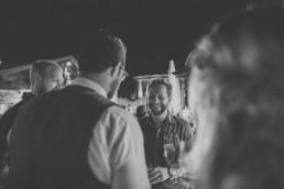 Natürliche schwarz weiß Aufnahme des Brautpaares mit ihren Gästen auf der Hochzeitsfeier einer Zelthochzeit fotografiert von Würzburger Hochzeitsfotografin Conny Schöffmann Photography