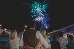 Brautpaar beobachtet eng umschlungen das stimmungsvolle Feuerwerk einer Stadtstrandhochzeit in Würzburg festgehalten von Hochzeitsfotografin Conny Schöffmann Photography, Würzburg