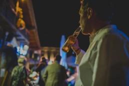Gast trinkt locker sein gekühltes Bier auf einer Stadtstrandhochzeit unter freiem Himmel festgehalten von Hochzeitsfotografin Conny Schöffmann Photography, Würzburg