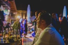 Stimmungsvolle Gäste beobachten das rege Partytreiben einer Stadtstrandhochzeit in Würzburg festgehalten von Hochzeitsfotografin Conny Schöffmann Photography, Würzburg