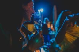 Strahlender Gast mit Sektglas in der Hand beobachtet die Tanzfläche einer Stadtstrandhochzeit unter freiem Himmel fotografiert von Hochzeitsfotografin Conny Schöffmann Photography aus Würzburg