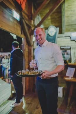 Glücklicher Gast hält ein Tablett voller Shots fotografiert von Hochzeitsfotografin Conny Schöffmann Photography, Würzburg