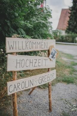Natürliches Willkommensschild im Freien aus Holz fotografiert von Hochzeitsfotografin Conny Schöffmann Photography aus Würzburg