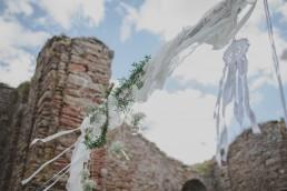 Stimmungsvoller Traubogen einer Ruinenhochzeit unter freiem Himmel fotografiert von Hochzeitsfotografin Conny Schöffmann Photography aus Würzburg