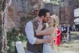 Stimmungsvoller erster Kuss nach einer Trauung im Freien fotografiert von Würzburger Hochzeitsfotografin Conny Schöffmann Photography
