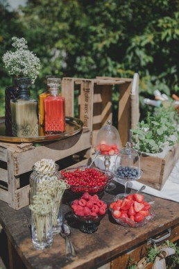 Liebevoll arrangierte Snacks auf einem alten Holztisch unter freiem Himmel fotografiert von Würzburger Hochzeitsfotografin Conny Schöffmann Photography