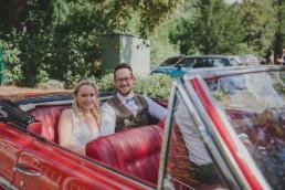 Glückliches Brautpaar sitzt in ihrem rotem Oldtimerhochzeitsauto fotografiert von Hochzeitsfotografin Conny Schöffmann Photography, Würzburg