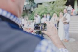 Enspannter Gast filmt das Brautpaar unter freiem Himmel fotografiert von Hochzeitsfotografin Conny Schöffmann Photography, Würzburg