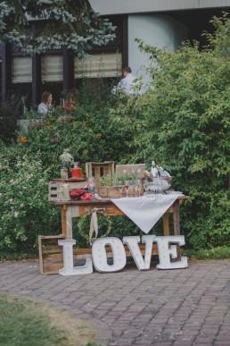 Liebevoll dekorierte Sektbar auf einem natürlichen Holztisch festgehalten von Hochzeitsfotografin Conny Schöffmann Photography aus Würzburg