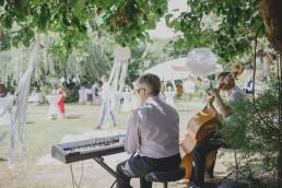 Entspannte Band spielt unter mit Traumfängern dekoriertem Baum Musik für die Gäste festgehalten von Hochzeitsfotografin Conny Schöffmann Photography aus Würzburg