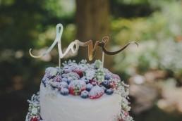 Goldener Love-Schriftzug auf der Hochzeitstorte einer Zelthochzeit im Freien festgehalten von Hochzeitsfotografin Conny Schöffmann Photography, Würzburg