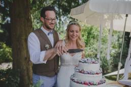 Brautpaar schneidet stimmungsvoll die Hochzeitstorte unter freiem Himmel an fotografiert von Würzburger Hochzeitsfotografin Conny Schöffmann Photography