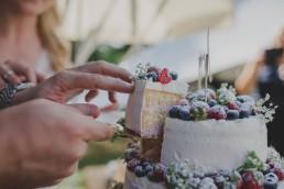 Bräutigam nimmt sich das erste Stück der natürlich dekorierten Hochzeitstorte einer Zelthochzeit in Würzburg fotografiert von Würzburger Hochzeitsfotografin Conny Schöffmann Photography