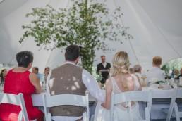 Braut und Bräutigam verfolgen locker der Rede eines Gastes auf einer Zelthochzeit in Würzburg fotografiert von Hochzeitsfotografin Conny Schöffmann Photography, Würzburg