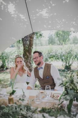 Entspanntes Brautpaar einer Zelthochzeit lacht glücklich in die Kamera festgehalten von Hochzeitsfotografin Conny Schöffmann Photography aus Würzburg